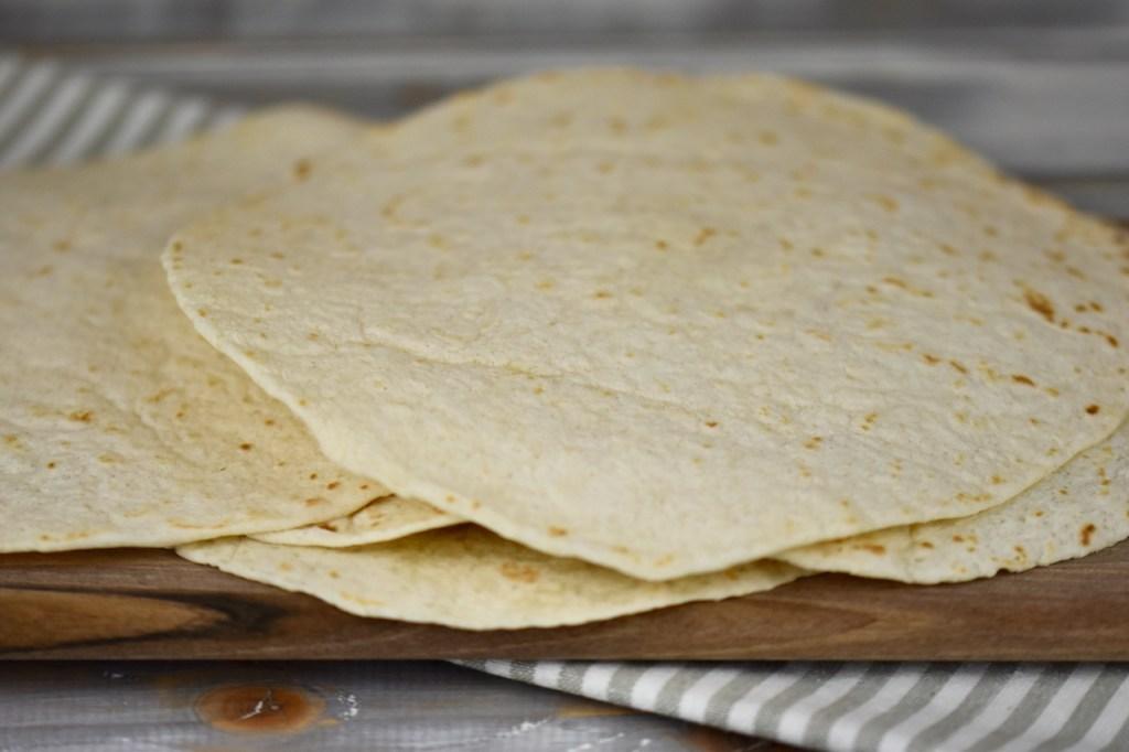 Tortilla Wraps übereinander gestapelt auf Holzbrett.
