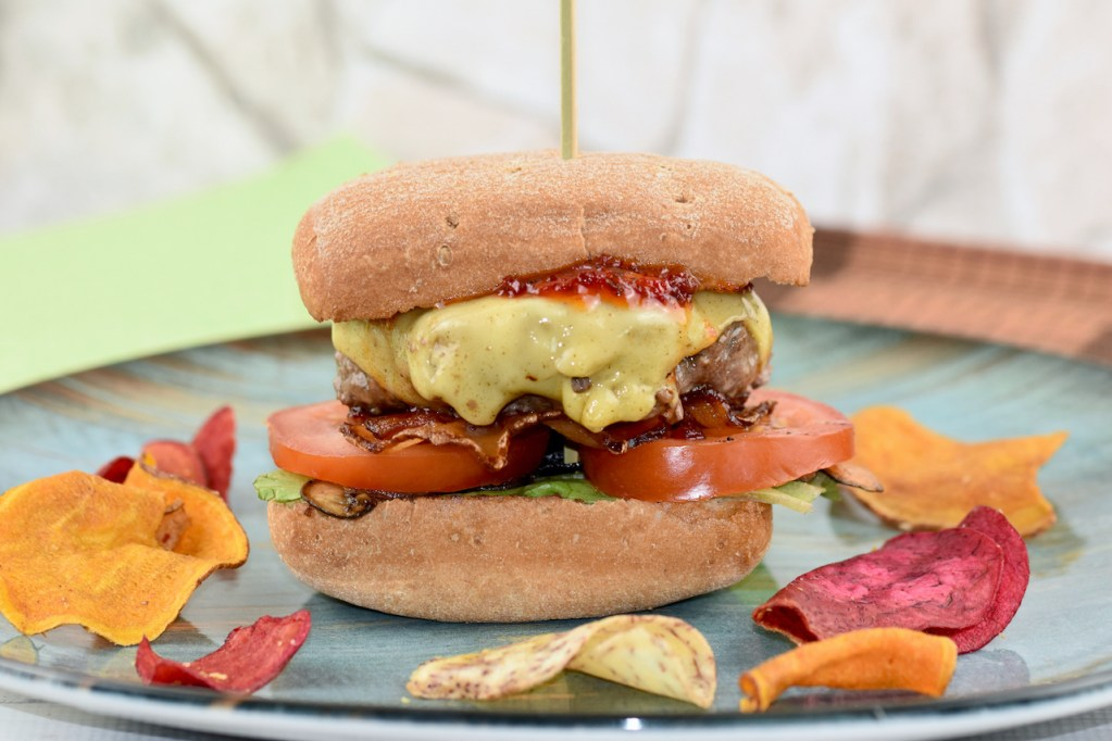 American Burger mit saftigem Rindfleisch-Patty auf blauem Teller. Hintergrund hell.