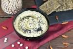 Klassisches Hummus aus Israel mit Schwarzkümmelsamen garniert. Es ist in einer schwarzen Schale und der Hintergrund ist dunkel.