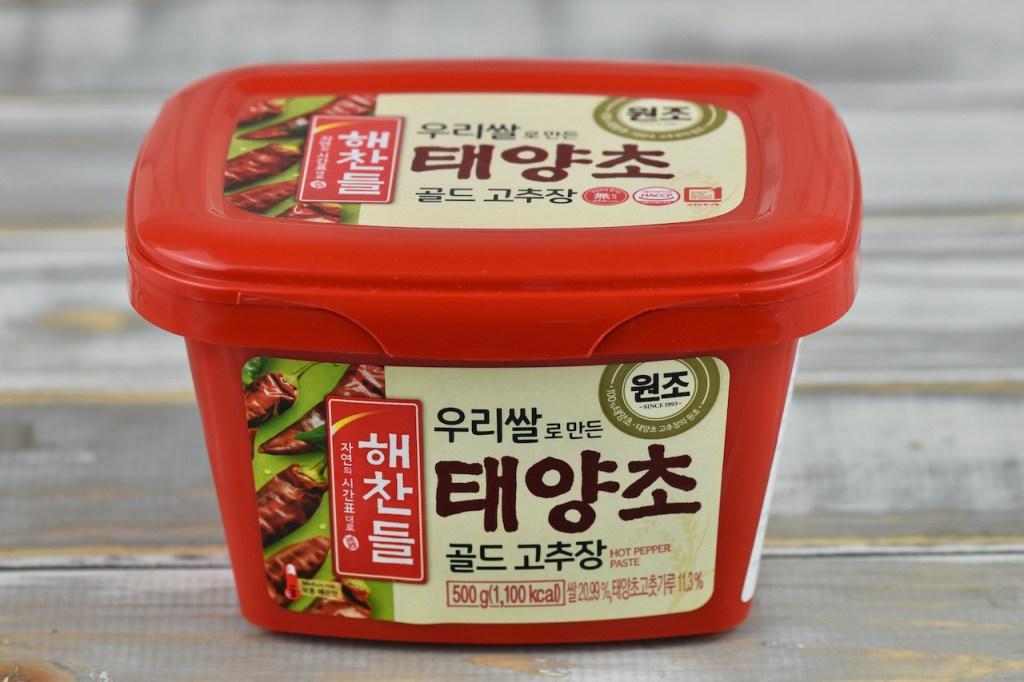 gekaufte koreanische Chilipaste (Gochujang). Die rote Verpackung ist mit koreanischen Schriftzeichen bedruckt.