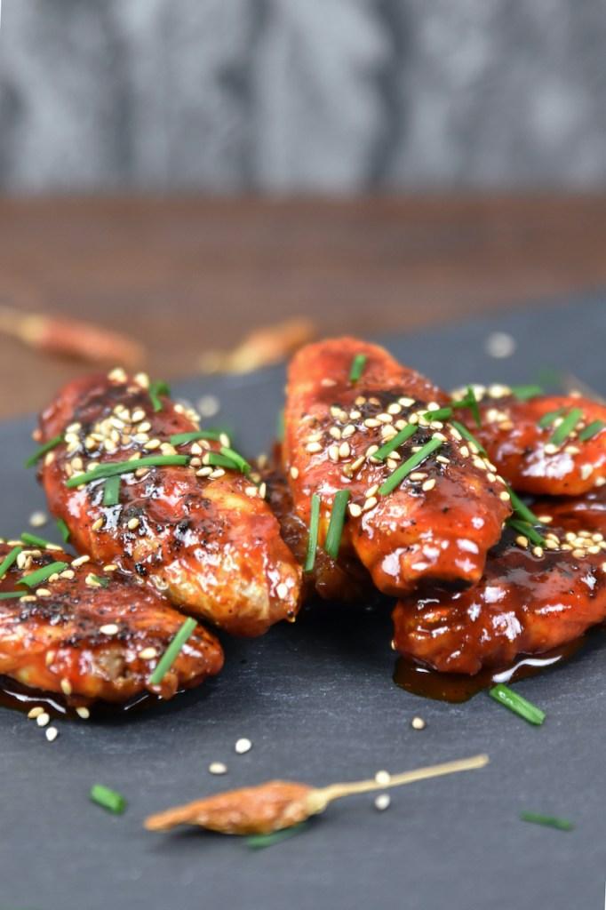 Koreanische Chicken Wings auf schwarzer Schieferplatte, garniert mit Schnittlauch und Sesam.