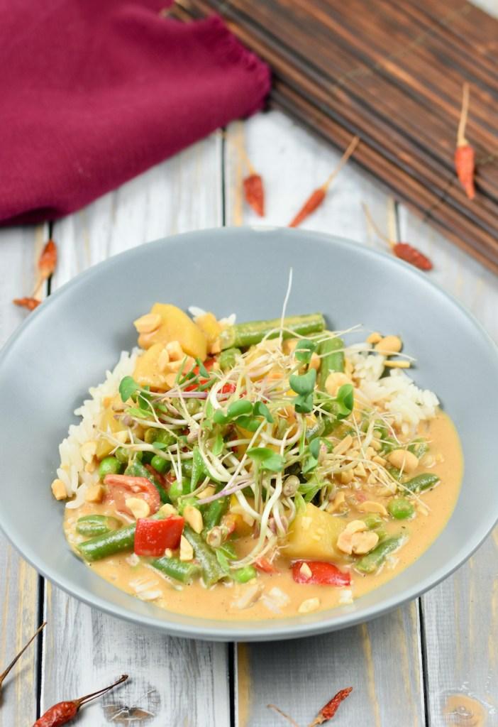Rotes Thai-Curry mit Kokosmilch in einem grauen, tiefen Teller. Hintergrund hell.
