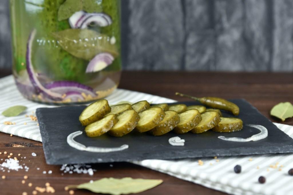 Senfgurken in Scheiben geschnitten auf einer Schieferplatte. Im Hintergrund steht das Einmachglas mit den restlichen Gurken - wilde Fermentation