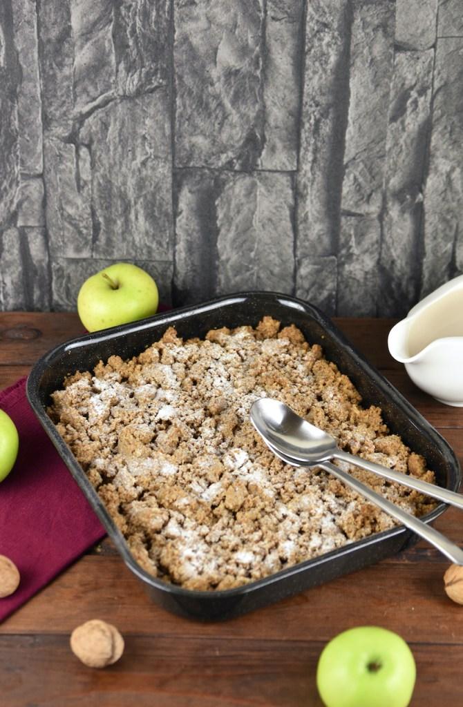 Apple Crumble mit Walnüssen und Haferflocken in einer Auflaufform. Hintergrund dunkel.