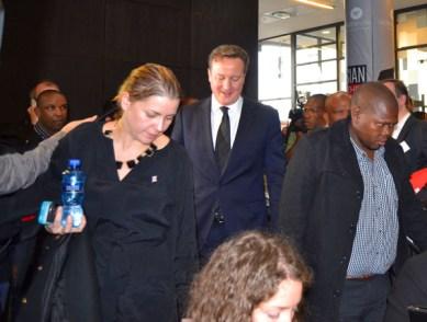 British Prime Minster David Cameron is ushered by security through the swarm of reporters. Photo: Nokuthula Manyathi