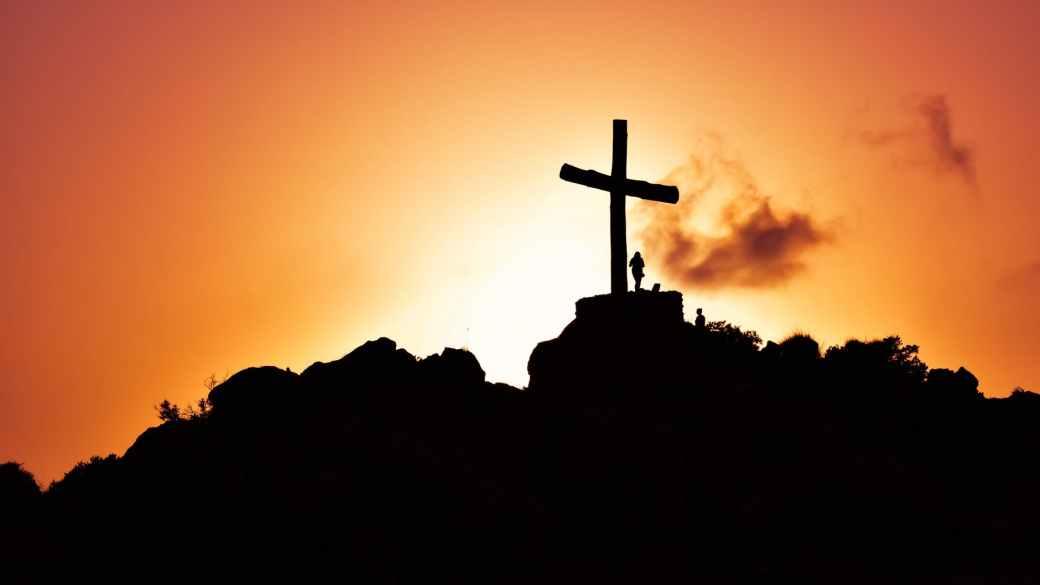 human standing beside crucifix statue on mountain