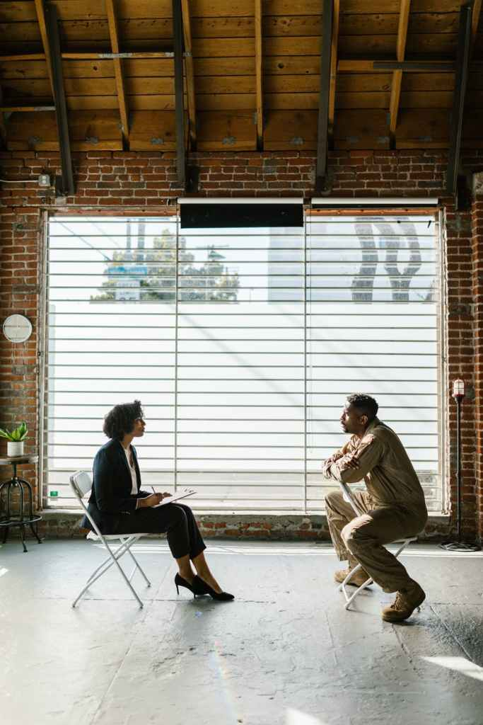 photo of man and woman sitting beside window