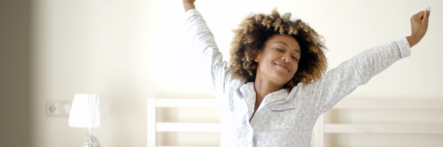 Healthy Woman stretching in bed room after waking up early
