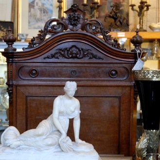 Victorian marble statue of reclining woman and carved headboard at Vintage Bank Antiques in Petaluma California