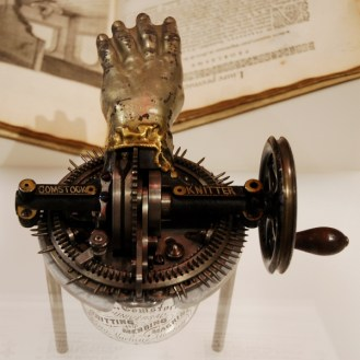 Metal hand and crank with glass base comprise the Comstock Knitter machine at the Cooper-Hewitt Smithsonian Design Museum in NYC