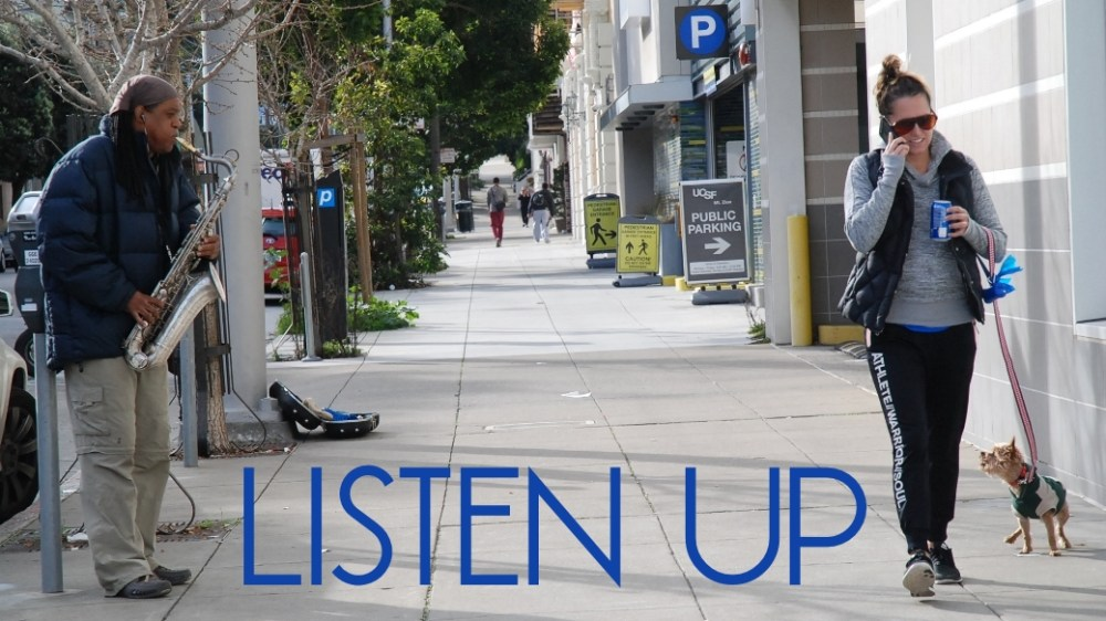 Yorkie barking at man playing saxophone San Francisco street