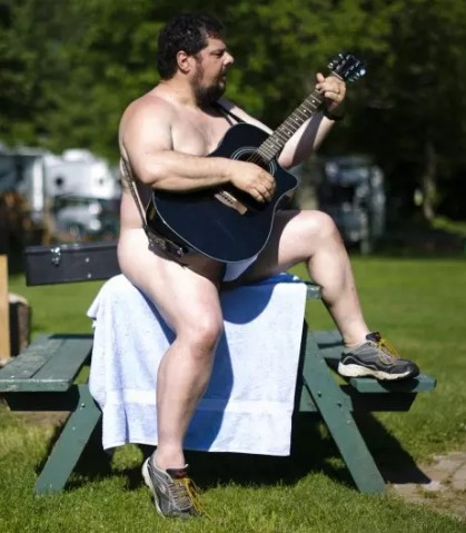 nude man playing guitar
