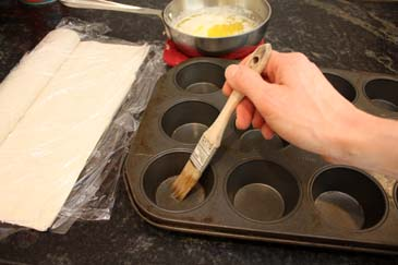 Brushing melted butter on muffin tin | ZoëBakes | Photo by Zoë François