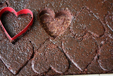 Cutting hearts out of a chocolate sheet cake with a heart-shaped cookie cutter | Photo by Zoë François