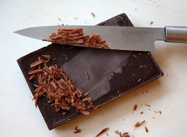 Scraping chocolate shavings off bittersweet chocolate bar | ZoëBakes | Photo by Zoë François