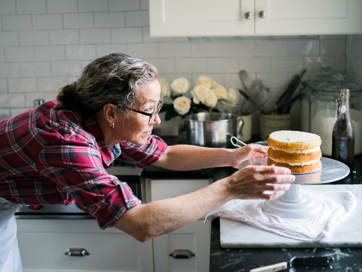 Zoë François assembling a coconut cream cake with toasted meringue frosting