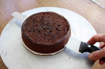 Cutting chocolate cake in half to create layers   ZoëBakes   Photo by Zoë François