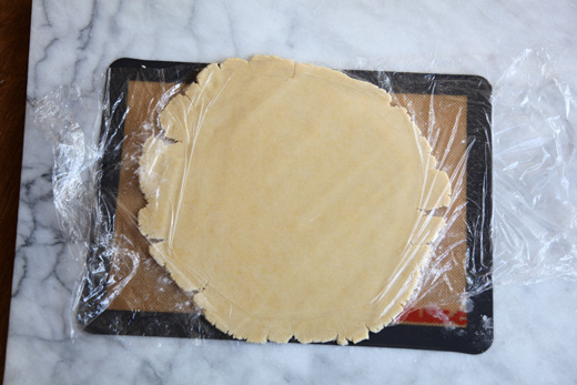 Almond tart dough rolled out and covered in plastic wrap