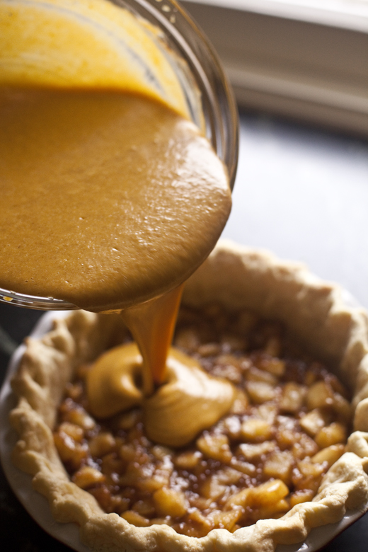 Pouring Pumpkin Pie Filling over Caramelized Apples in Pie Crust | ZoeBakes | Photo by Zoë François