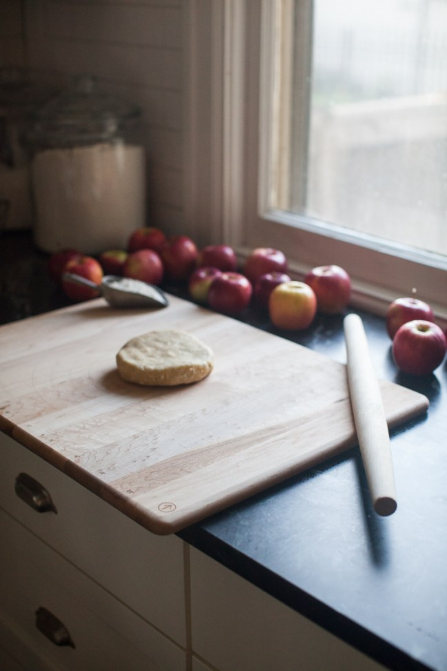 A disk of pie dough on a cutting board with a rolling pin, flour and a dozen apples.