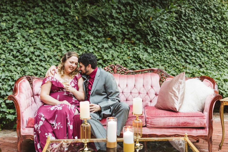 wedding guests canoodling on a pink couch | Reasons to consider having a small, intimate wedding that you may not have considered