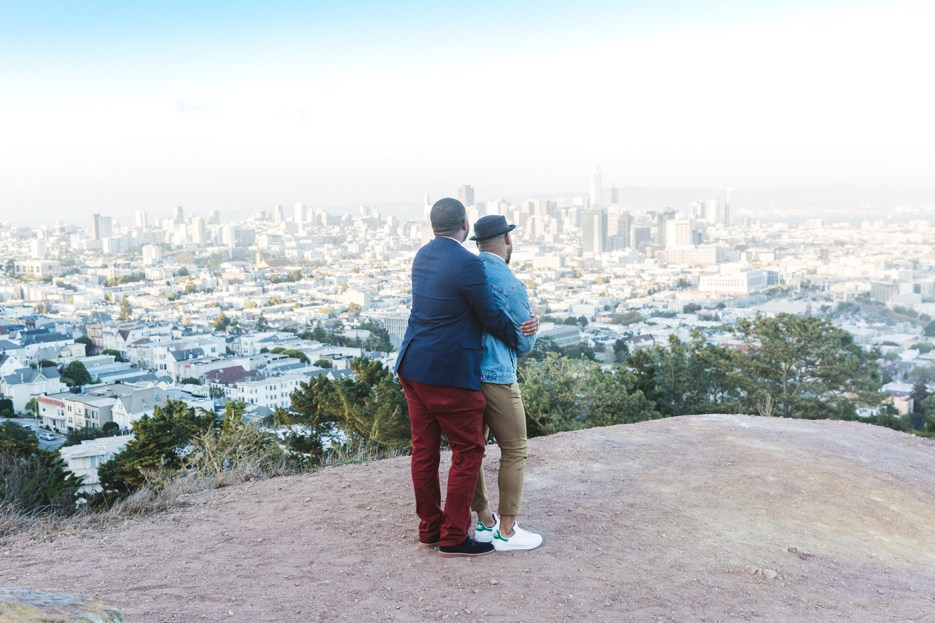 two engaged men dance overlooking city of san francisco