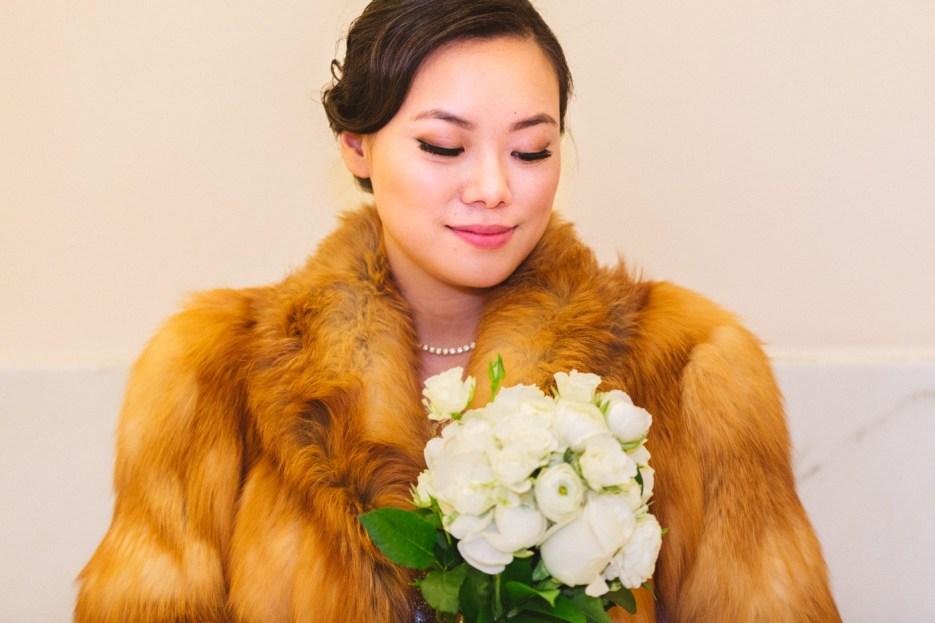 bride in fur coat looking down at flowers