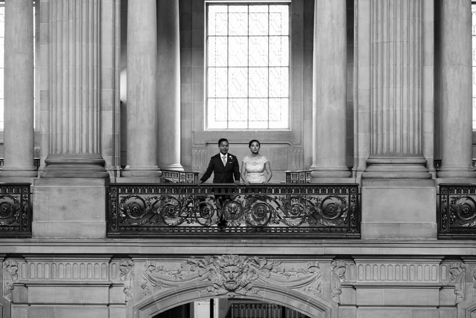 black and white classic image of bride and groom by city hall balcony
