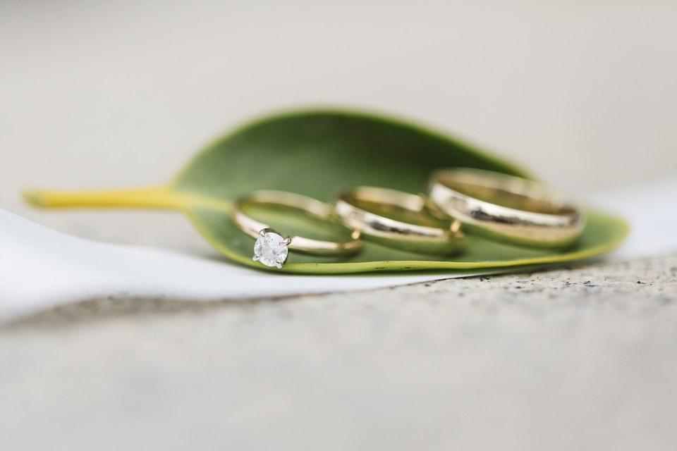 macro shot of wedding and engagement ring outside san francisco city hall