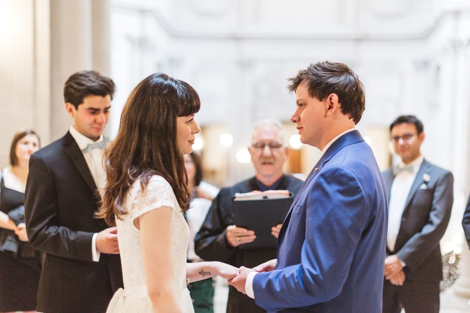 couple marrying at city hall looking into each other's eyes during wedding ceremony in rotunda