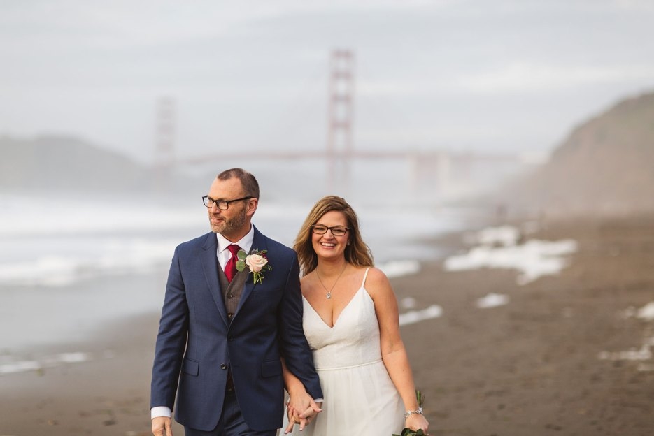 couple on wedding day walking down baker beach san francisco