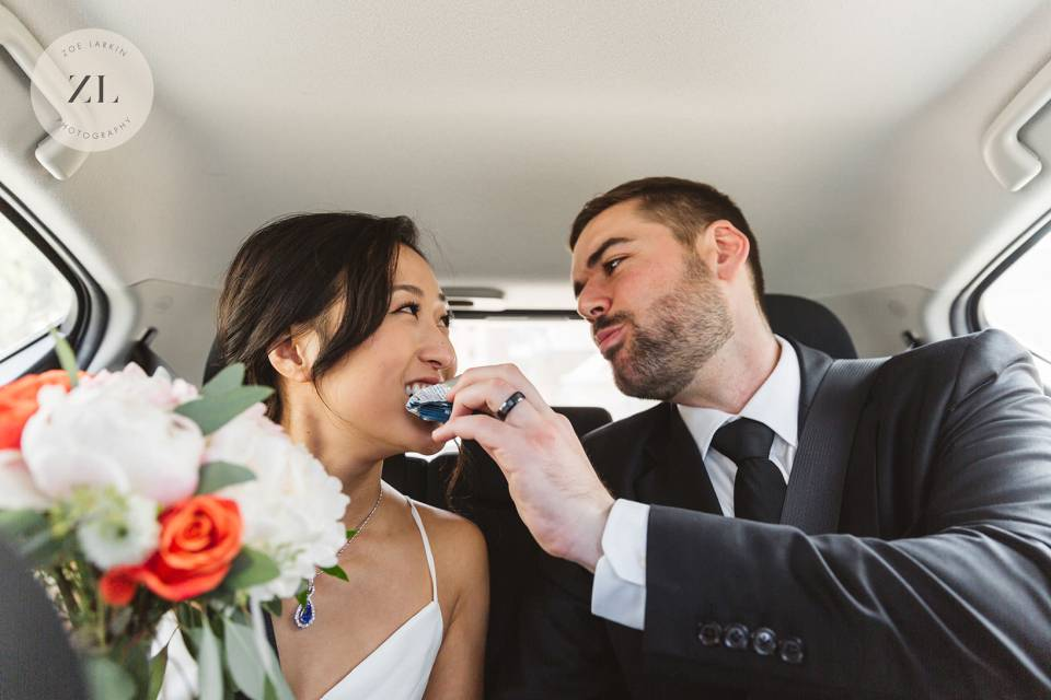 groom feeding bride a snack in the back seat of the Uber after their San Francisco wedding day