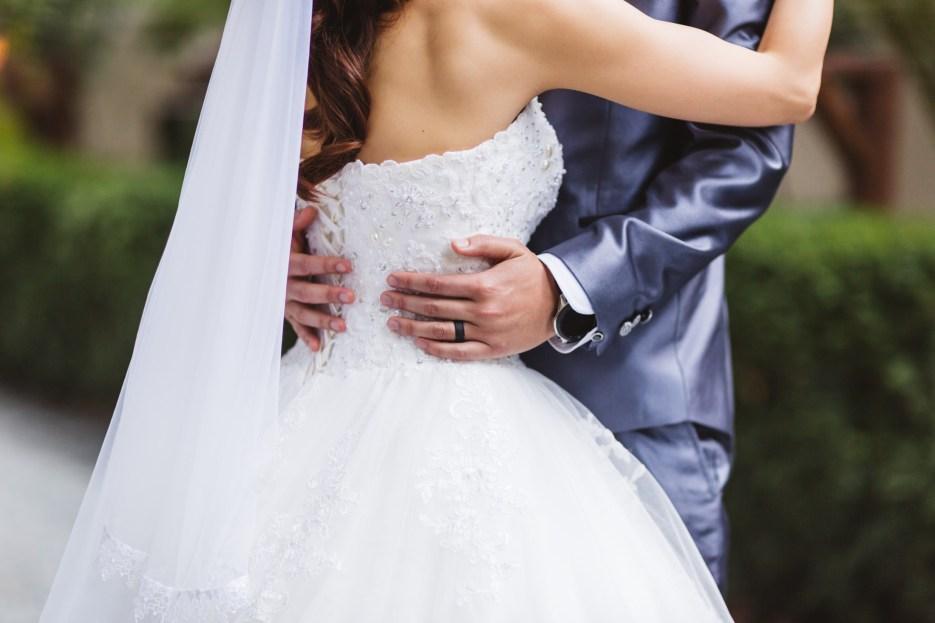 detail of groom holding bride's waist