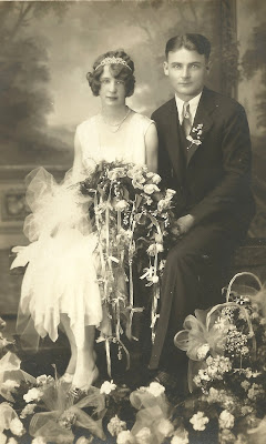 1920s wedding photography of a couple sitting and holding a long trailing bouquet