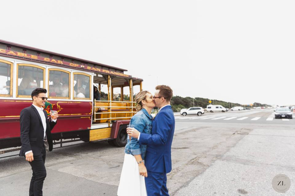 wedding couple kissing on Ocean Beach San Francisco with Hornblower cable car in background
