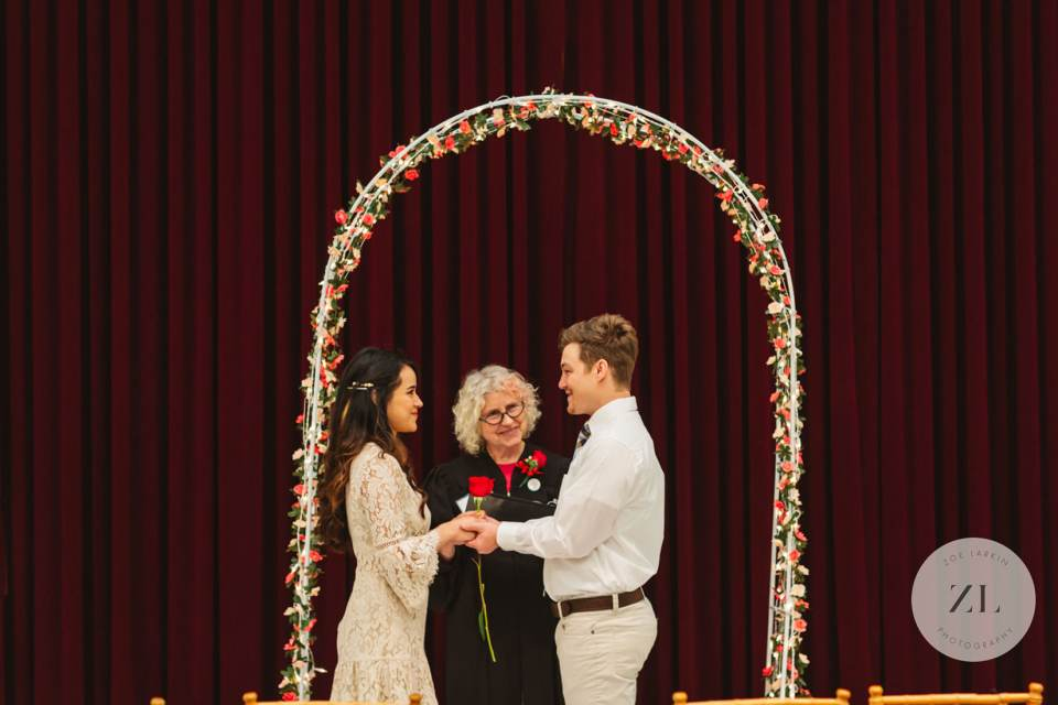 couple getting married under the special valentine's day arch