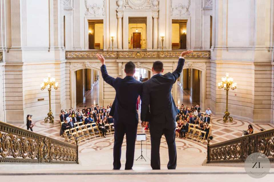 same sex wedding couple waving to guests from top of staircase at sf city hall