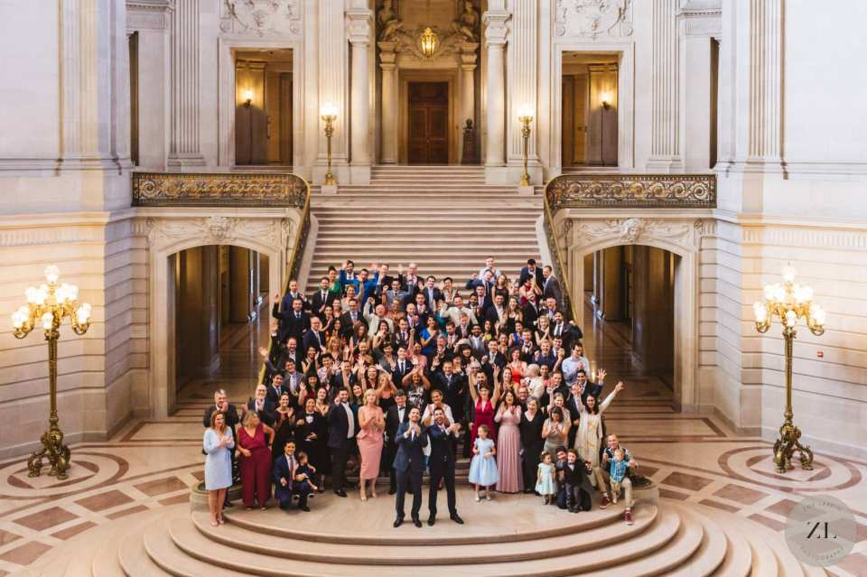 group shot with 150 guests standing on grand staircase at San Francisco City Hall