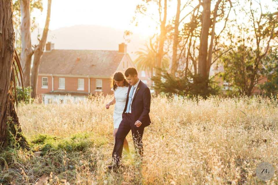 wedding couple walking through long grass backlit by sun in presidio of san francisco for lockdown wedding