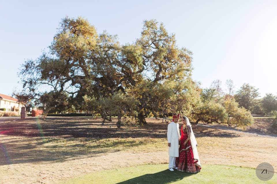 indian wedding couple under the oak tree at the club at ruby hill