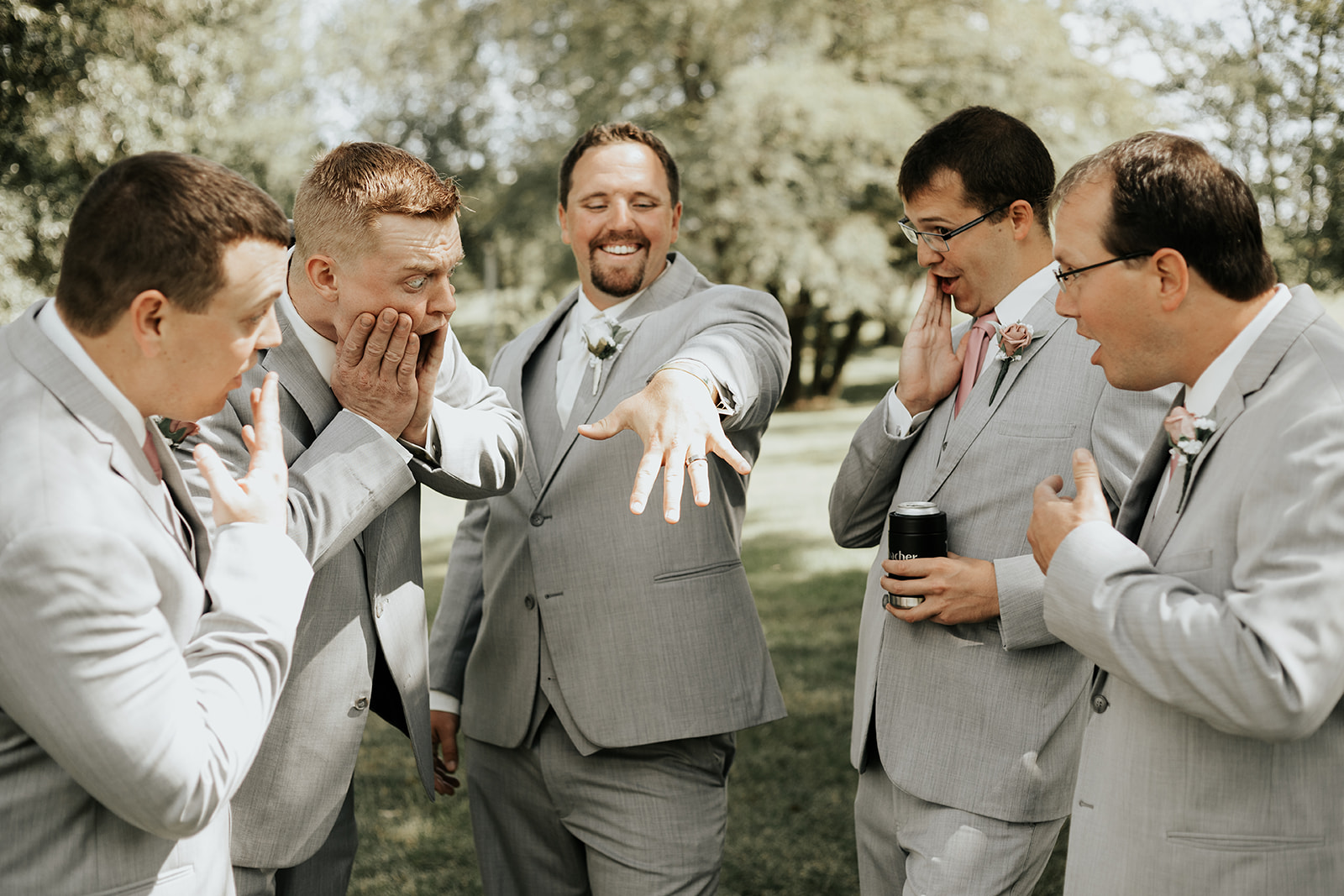 funny groom showing off ring to groomsmen photo