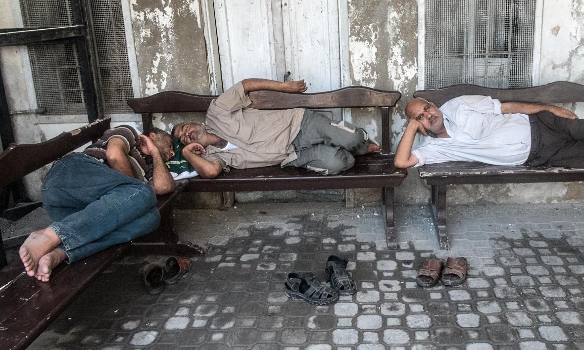 Παλαιστίνιοι ξεκουράζονται στα παγκάκια στο προαύλιο της εκκλησίας
