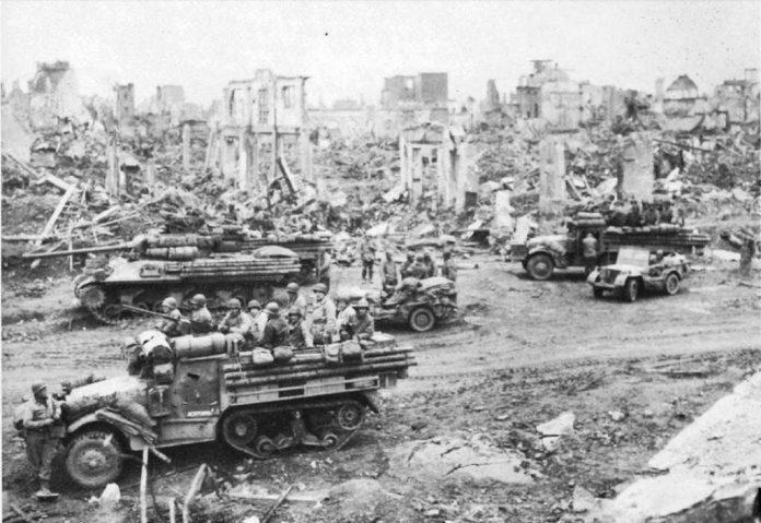 Un claro ejemplo de los medios pertenecientes a una división blindada: Jeeps, camiones y semi-orugas M-3A1 junto a un caza tanques M-36 disponen de una pausa junto a las ruinas de la ciudad de Dueren, Alemania.