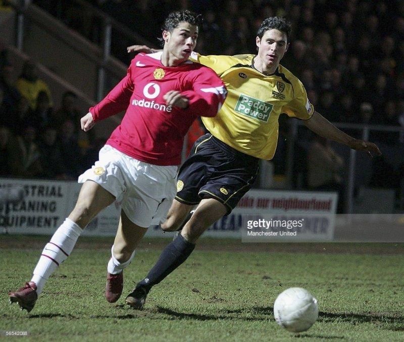 Un giovane Cristiano Ronaldo viene pressato da un giocatore del Burton. (John Peters/Manchester United via Getty Images)