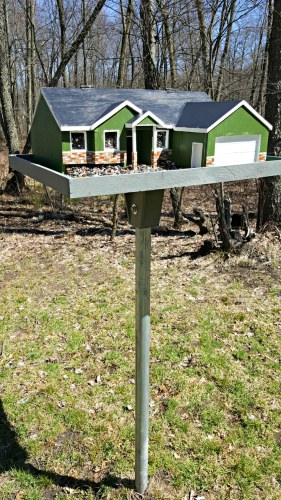 a diy bird feeder mounted on a post in the front yard