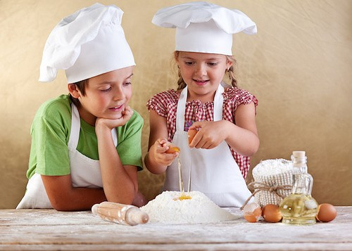Kids preparing a cake - starting with flour and eggs