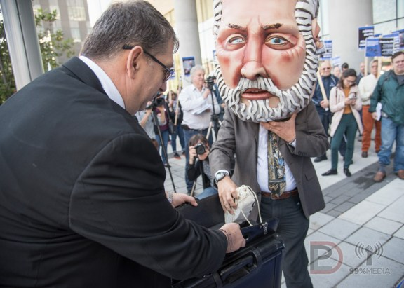 Une mascotte du Premier ministre Philippe Couillard dépose des sacs d'argent dans la valise d'un représentant des PPP.