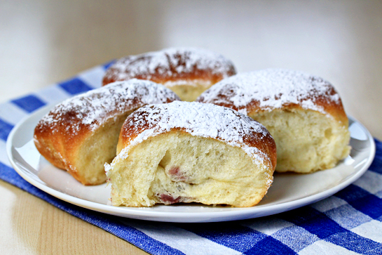 sweet jam filled buns on a plate dusted with sugar