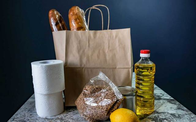 A selection of groceries including vegetable oil, toilet paper, and loaves of bread rest atop a table.