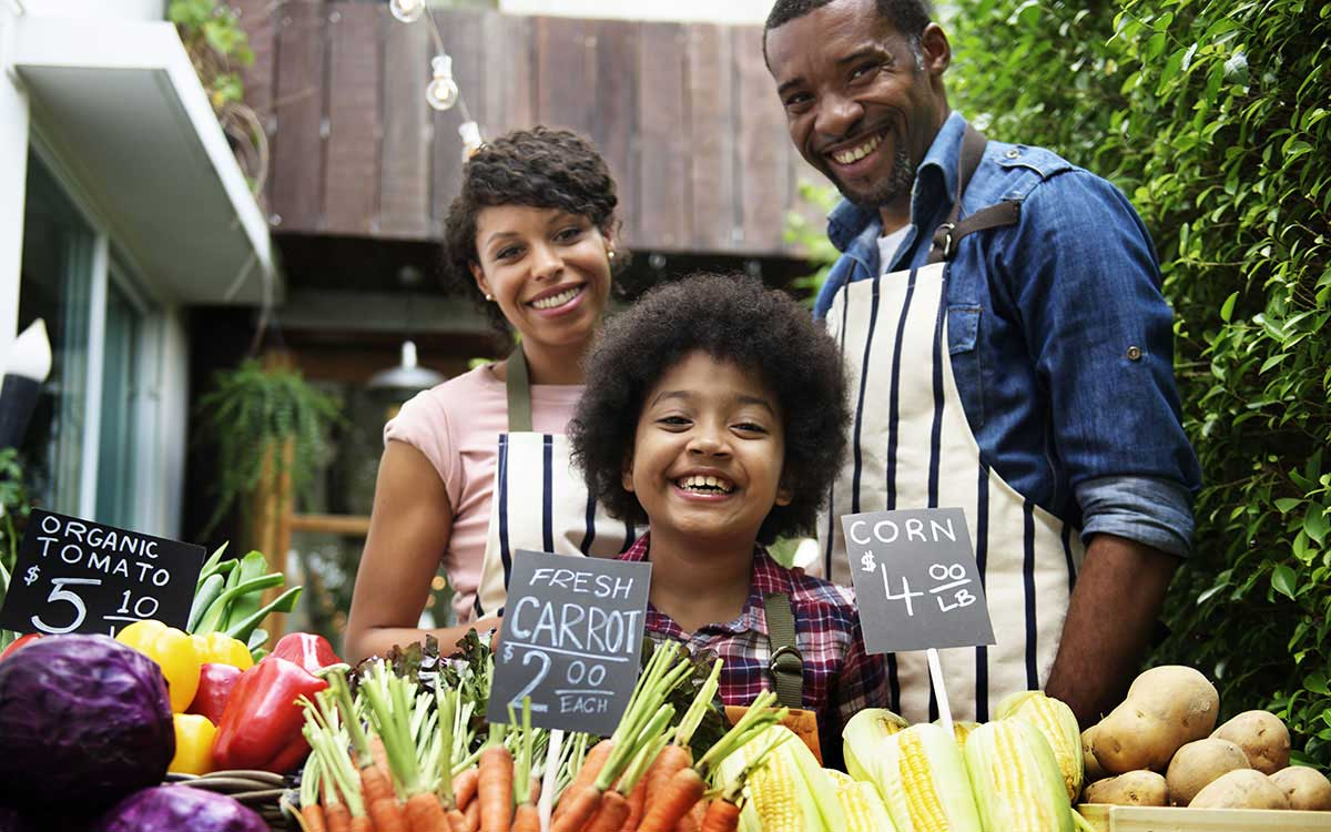 A family poses happily behind a vegetable stand.